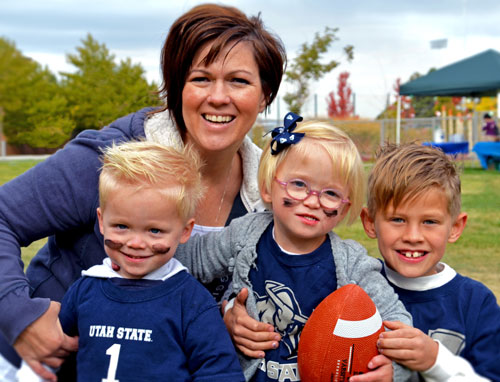 a Sound Beginnings teacher and students with USU football gear