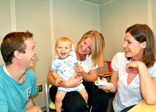 a happy baby getting a hearing screening with parents and audiologist