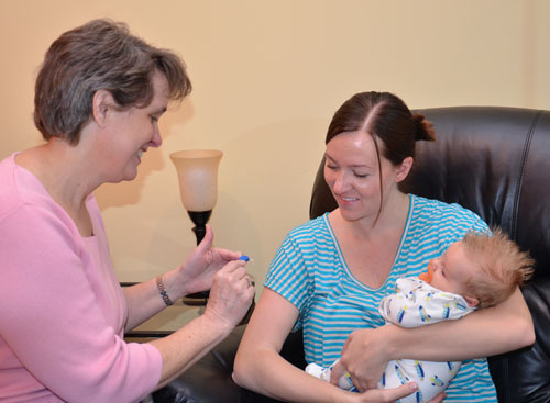 Dr. Karen Munoz explaining a hearing aid's functionality to a mother holding her baby