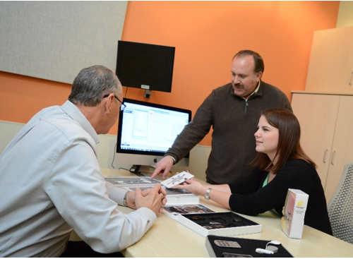 Three professionals discussing audiology technology