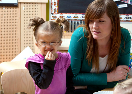 a teacher and a young child in a classroom setting